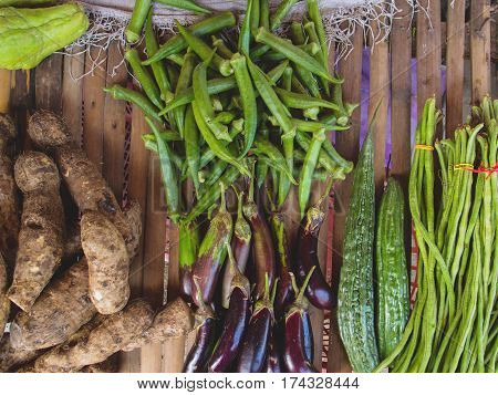Sweet potato and eggplant with other vegetables on wood table. Farm market in tropical country. Exotic vegetables on table for sell. Fresh ripe vegetables of Philippines. Natural still life flat photo