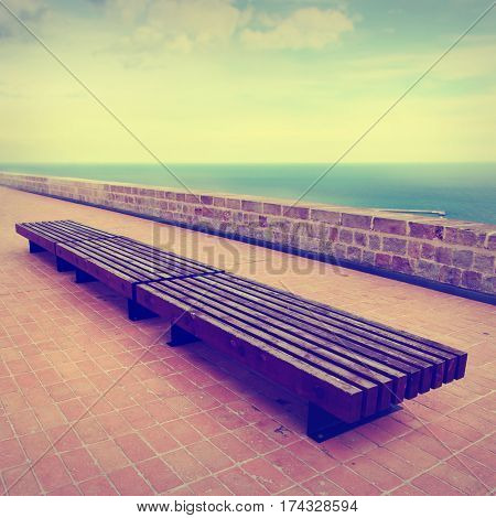 Vintage style photo of bench near the sea.
