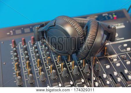 DJ Mixer with knobs and black headphones. Music