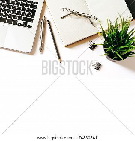 Modern minimalistic work place. White office desk table with laptop, coffee cup, clips, glasses, notebook, pen and pencil. Top view with copy space, flat lay