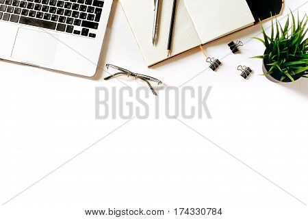 Modern minimalistic work place. White office desk table with laptop, clips, glasses, office plant, notebook, pen and pencil. Top view with copy space, flat lay