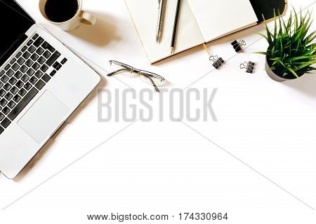 Modern minimalistic work place. White office desk table with laptop, coffee cup, clips, glasses, office plant, notebook, pen and pencil. Top view with copy space, flat lay