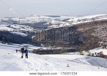PEAK DISTRICT UK - CIRCA 2012: Senior couple hiking up Kinder Scout in winter snow. Hayfield Peak District UK