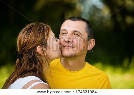 Affectionate father being kissed by her adult caring daughter