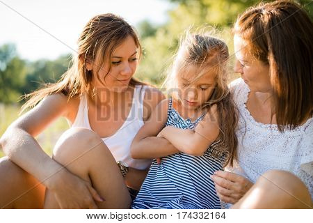Family consoling cute young little girl who is upset