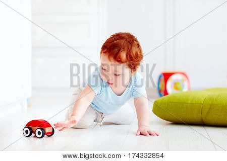 Cute Infant Baby Playing With Wooden Toy Car At Home
