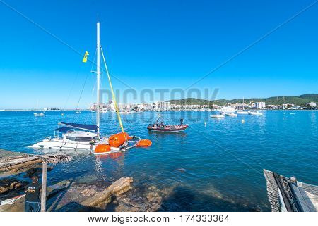 Editorial:  Sant Antoni De Portmany, Ibiza, November 6th, 2013:   Post thunderstorm blues.  Bright morning sees a dive crew work to recover a crippled partially submerged catamaran boat that broke free from its mooring during an overnight storm.