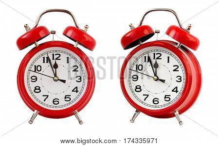 Red retro alarm clock at twelve o'clock isolated on white background. Midnight midday.
