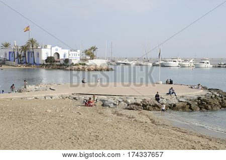 MARBELLA, SPAIN - FEBRUARY 26, 2017: People at the beach next to the marina in a sunny day of february in Marbella Andalusia Spain.