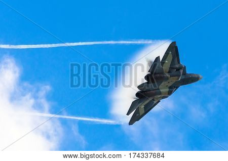 Battle fighter jet flying dives breaking clouds on a blue sky disruption of air flow. Russia. Moscow 29 August 2015