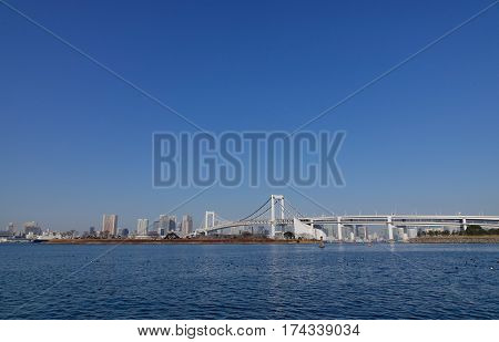 Tokyo Bay with Rainbow Brigde in Tokyo Japan. A number of Japan's most important ports are located in Tokyo Bay.
