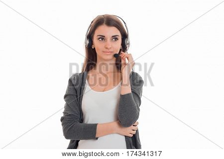 serious young girl in gray jacket and headphones worth straight and looks toward isolated on white background