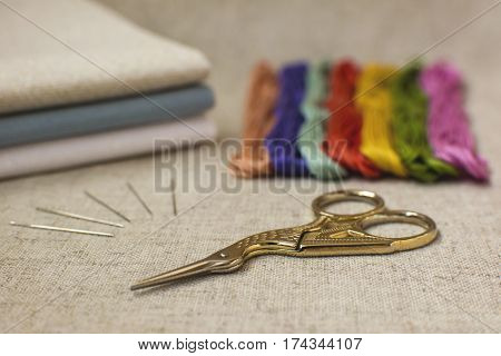 Embroidery and cross-stitch set on a natural linen background. Focus on the scissors.