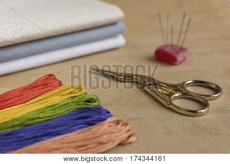 Cross-stitch kit for embroidery consisting of scissors needles multicoloured threads and canvas. Focus on the scissors.