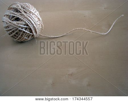 Close up of a roll of twine on woodden board