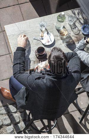 Birdseye of well dressed people drinking coffee in a street bar