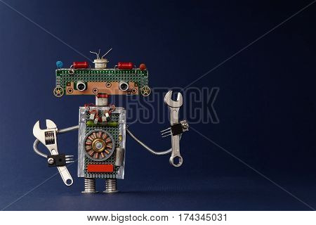 Hand wrench adjustable spanner robot handyman on dark blue paper background. Cute robotic toy made of electronic circuits, chip capacitors vintage resistors.