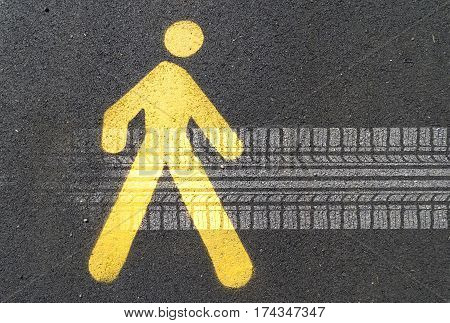 Painted sign on asphalt for pedestrian lane and tire track. Concept: road hazards for pedestrians