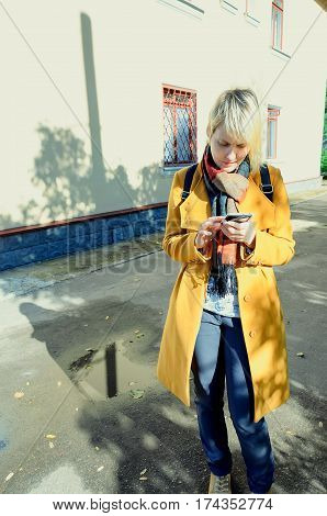 young girl standing on the street in the spring coat and looking at the phone, email and social networks