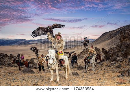 Kazakh Eagle Hunter in traditionally trained golden eagles riding horse in a desert mountain. OlgeiWestern Mongolia.