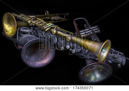 A collection of instruments including two trumpets a C Melody saxophone and a metal clarinet.