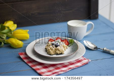 Porridge with berries fresh strawberries and blueberries. Strewing with powdered sugar. Tasty breakfast