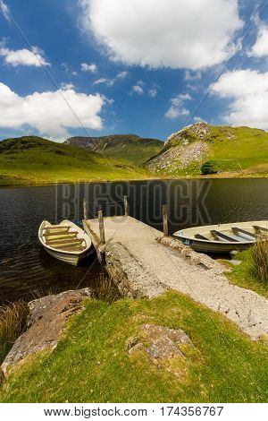 Two boats moored to Jetty by small lake. Llyn y Dywarchen Reservoir Rhyd Ddu Gwynedd Wales United Kingdom