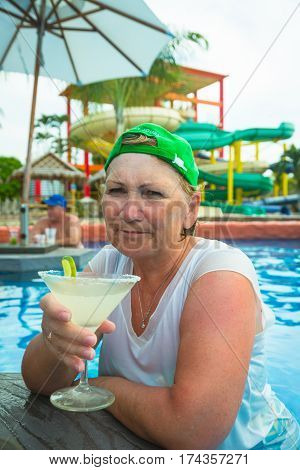 Portrait of elderly woman in green baseball cap sitting in swimming pool with glass of mojito and looking at camera with displeased face