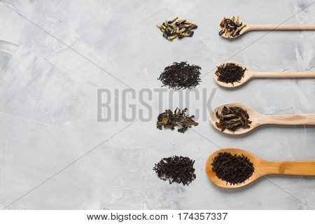 Wooden Spoons With Different Tea Leaves On Grey Concrete Backgro