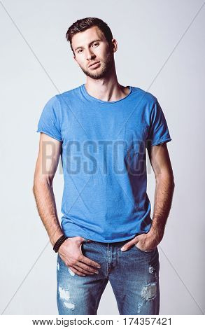 Studio fashion shot: portrait of a handsome young man wearing jeans and shirt