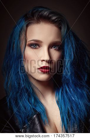 Closeup studio portrait of a beautiful young woman with blue hair
