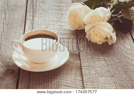 Soft full blown white roses with cup of black coffee on wooden board with copy space. Toned image. Close up. Selective focus.