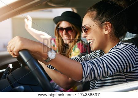 Two Lively Young Women Driving In A Car