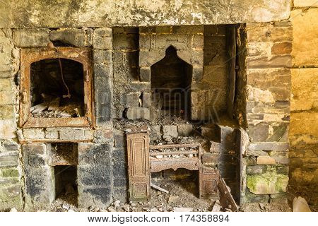 Interior of derelict building with fireplace and peeling walls.