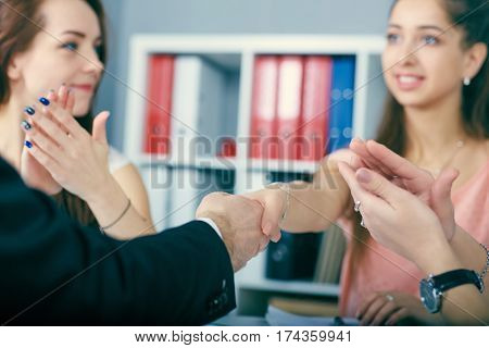 Close up of business handshake in the office. Serious business and partnership concept. Partners made deal sealed with handclasp.
