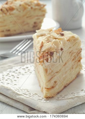 Piece of multi layered cake. Mille feuille dessert. Crumbs decorated torte on white doily upon wooden table. Food background, blur. Selective focus on the front.