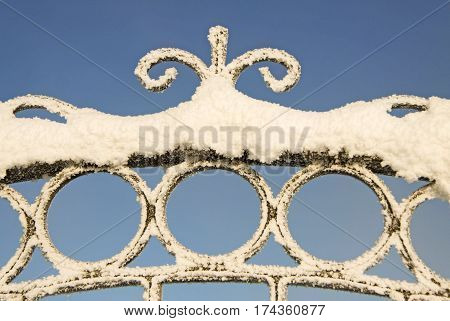 Snow on the wrought iron fence with the blue sky on the background