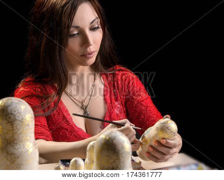 Young woman during the process of  painting handmade nested doll - russian matryoshka, dark background