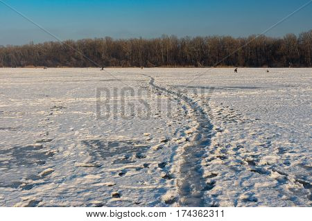 Winter landscape with pedestrian path over frozen Dnepr river in the same city Ukraine