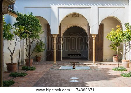 MALAGA, SPAIN - FEBRUARY 16, 2014: A quiet yard at Alcazaba, a castle of Malaga, with orange trees at pots, fountains and arch entrance in arab style, Andalusia, Spain.