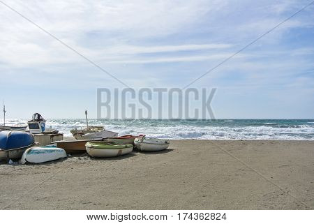 CABO DE GATA SPAIN - FEBRUARY 9 2016: Fishing boats at the shore of national park Cabo de Gata near Almeria (Andalusia Spain) and sea waves on the background.