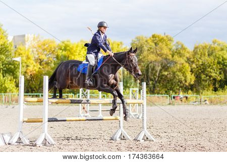 Young horseback sportswoman jumping over obstacles on show jumping competition