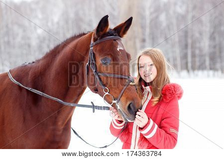 Young teenage girl spending time with her friend bay horse in winter park. Equestrian hobby background