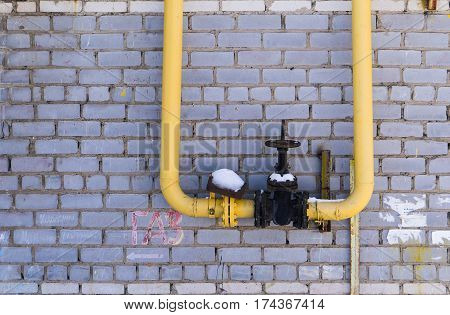 gas equipment pipes and shut-off valve on the background wall.
