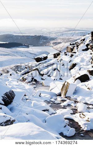 Snow covered countryside in winter with Kinder Reservoir viewed from Kinder Scout Peak District UK