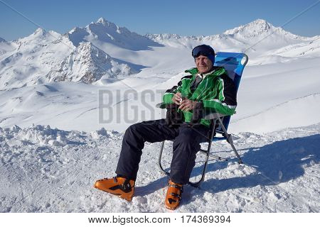 Man in alpine skiing clothes sits in a chaise lounge and looks at mountains