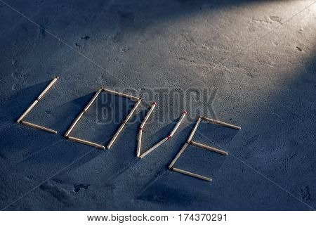 Abstract texture of concrete and blue paint plaster. On the texture matches arranged in the form of the word Love. Selective focus. From the top right corner of the light falls on the letters. Sunlight highlights the active word Love on a concrete backgro