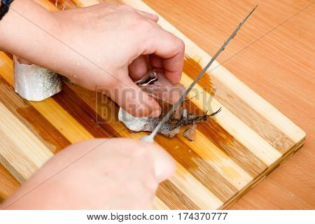 Female Hands With Knife Slicing Fish Hake