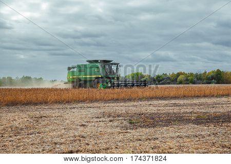 Kiev Region Ukraine - October 6 2013: John Deere 9610 Maximizer combine harvester harvesting soybeans on the field under stormy clouds