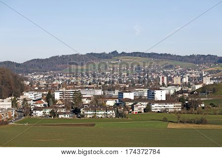BERN SWITZERLAND - DECEMBER 26 2015: Aerial view of the buildings in the district surrounding the city. Slight hills and the forest in the distance during winter day with no snow can be seen